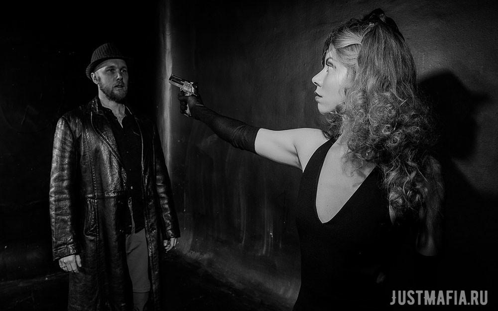 Ведущая Мафии Ольга в роли мирного жителя направляет пистолет на подозрительного типа