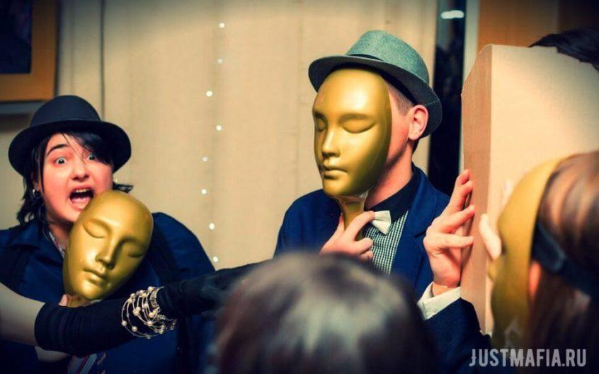 Игроки закрывают лицами маски, девушка в шляпе снимает маску и эмоционирует