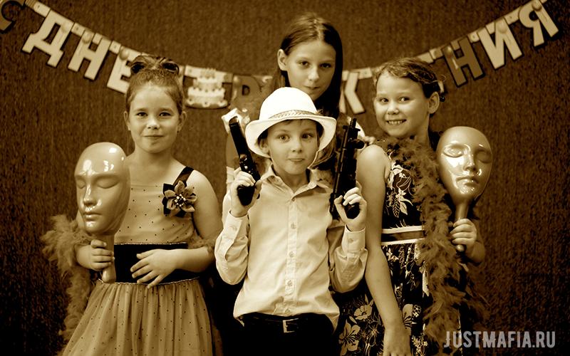 Дети с реквизитом для Мафии на фоне растяжки «С днем рождения»