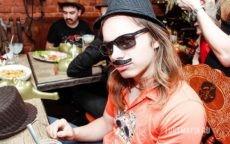 Молодой человек в шляпе, солнечных очках и с бутафорскими усами