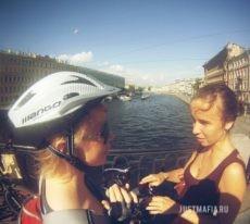 Участница квеста в шлеме разговаривает с девушкой на мосту