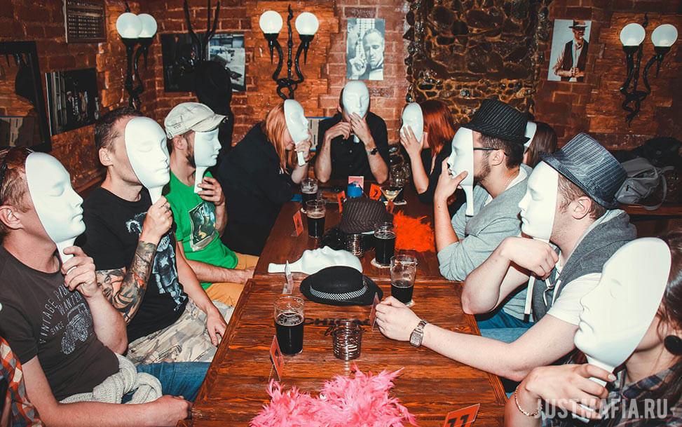 Игроки в Мафию сидят за столом и закрывают лица масками