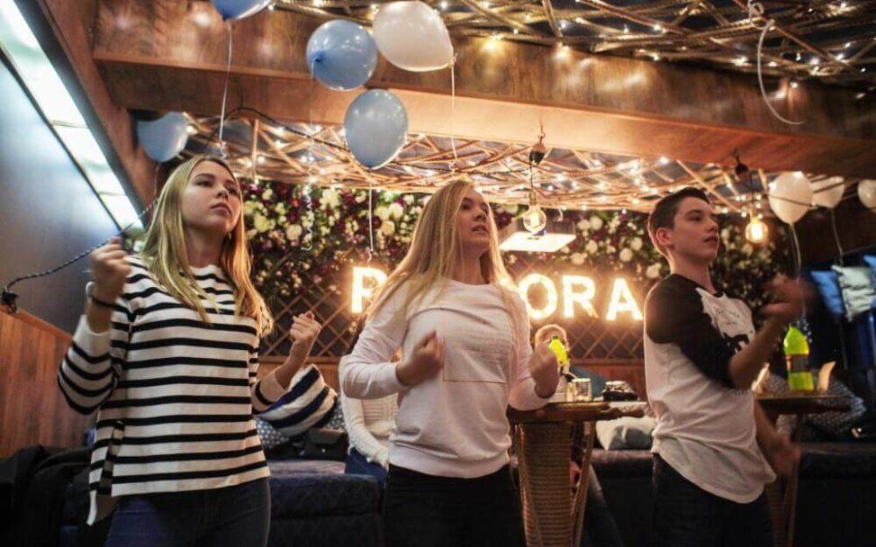 Подростки танцуют в ресторане