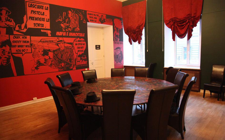 Зал в бордовых и зеленых тонах, круглый стол, высокие кожаные стулья