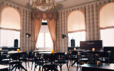 Светлый зал, высокие окна, столики, стулья, свечи, рояль