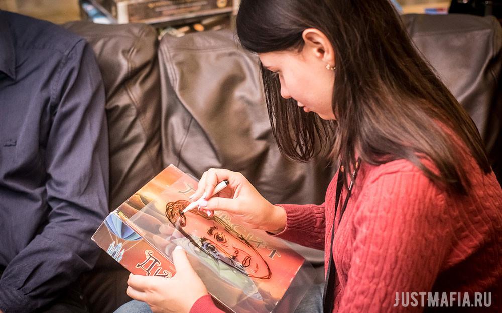 Девушка рисует портрет мужчины на коробке с игрой Диксит