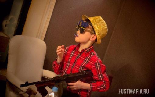 Мальчик в очках с усами, шляпе и с игрушечным автоматом